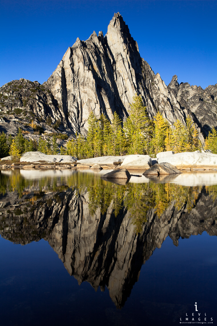 Prusik Peak and Larch trees reflected in alpine lake on a fall afternoon, the Enchantments, Washington, USA