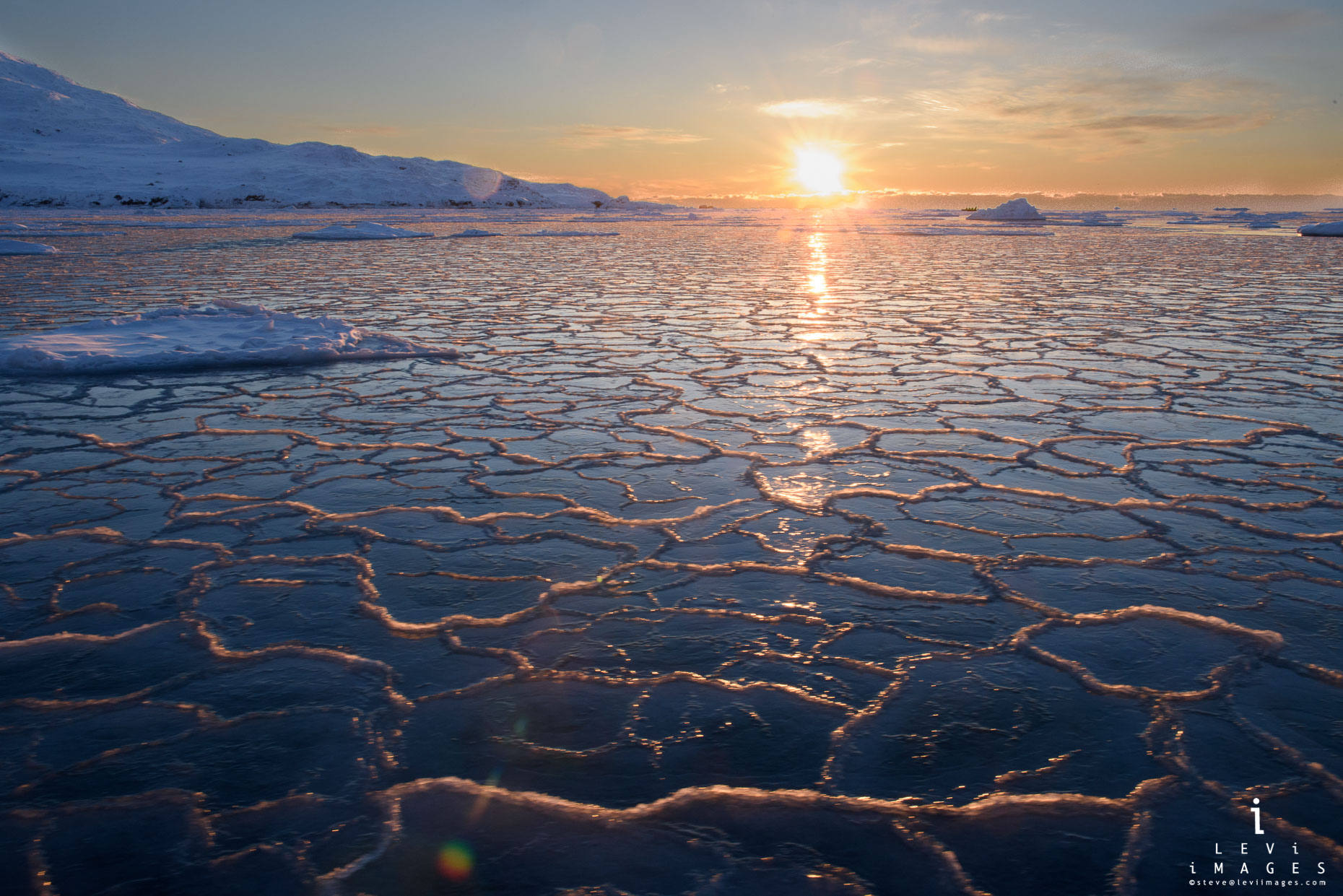 Sunset over honeycomb ice in fjord. Svalbard, Norway