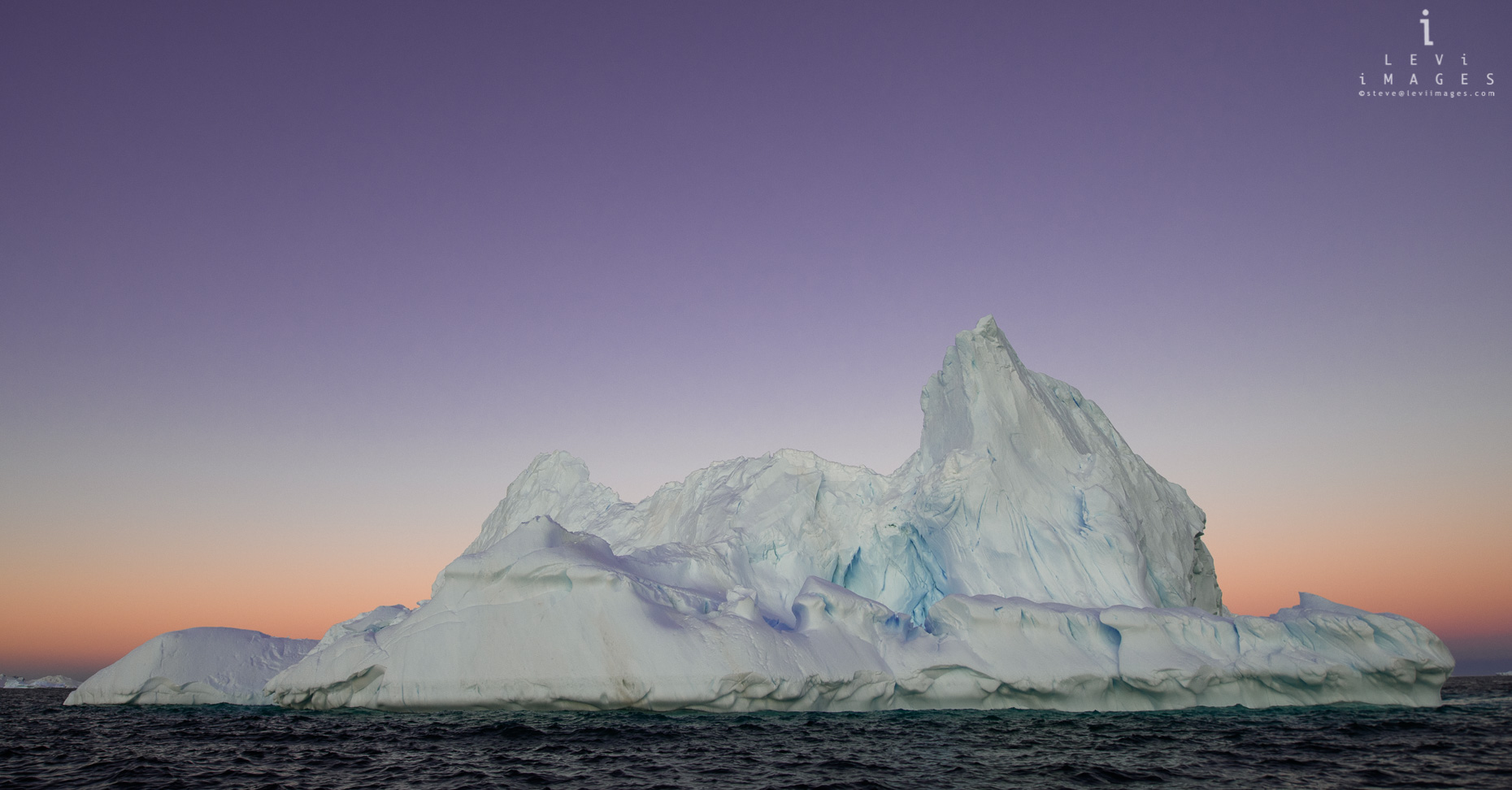 An iceberg bathed in the purple post-sunset light, Antarctica