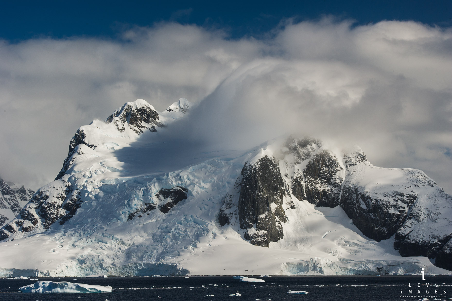 Clouds rush over glacial covered mountains. Lemaire channel, Antarctica