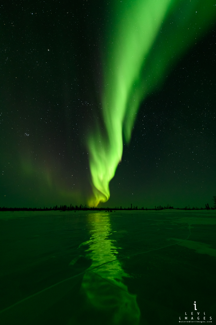 Northern lights reflected on lake ice. Manitoba, Canada