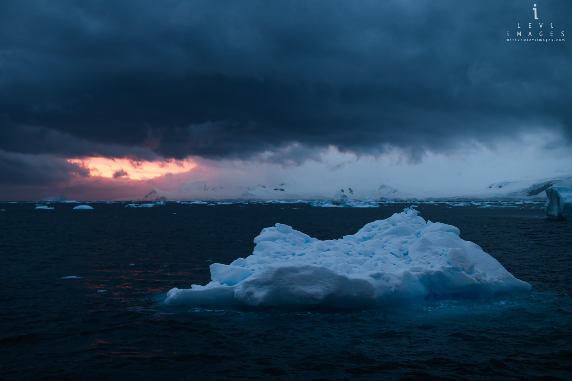 Dramatic sunset breaks through storm clouds over Antarctic landscape