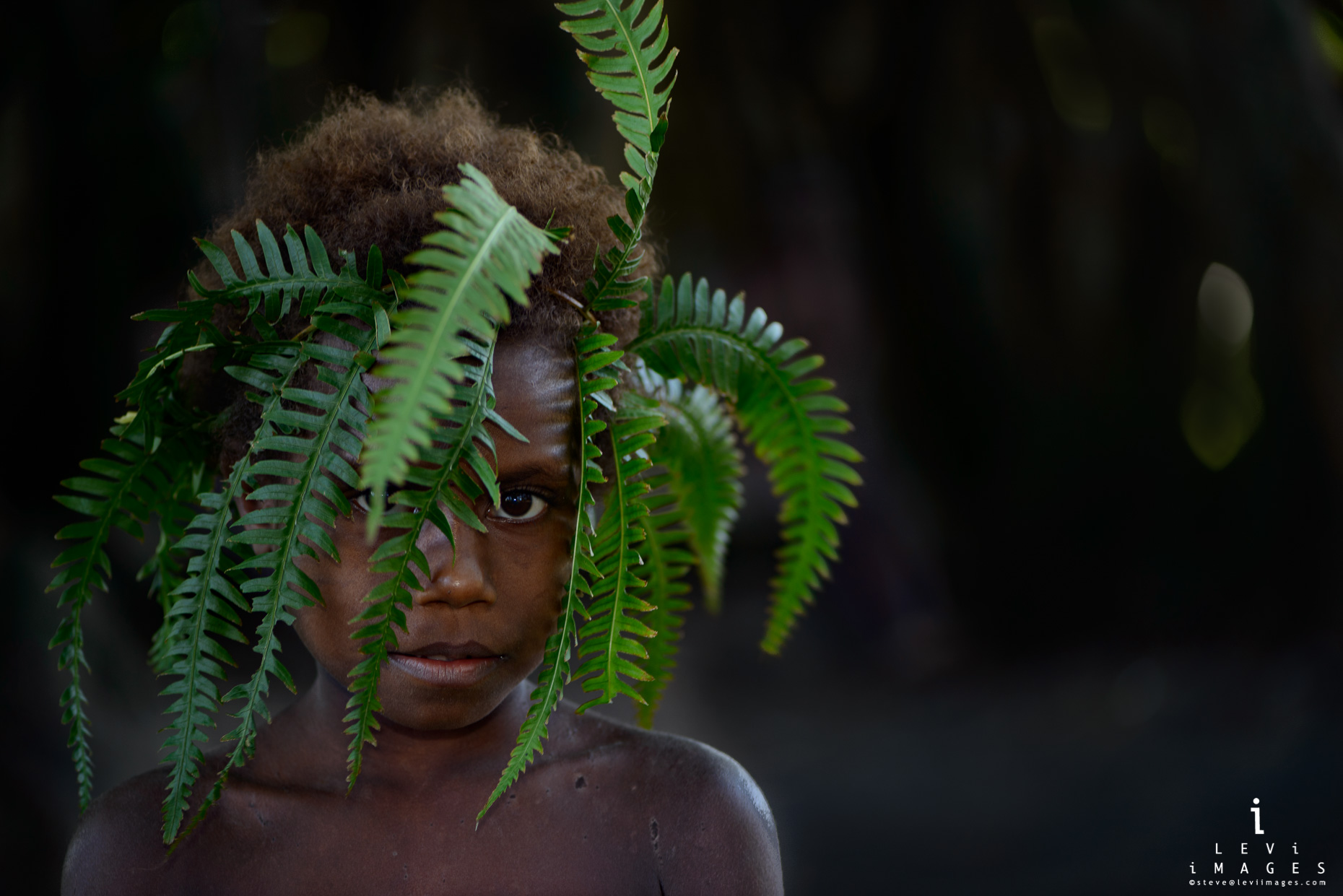 Native girl wears a simple headpiece made from fern frons. Tanna Island.Vanuatu
