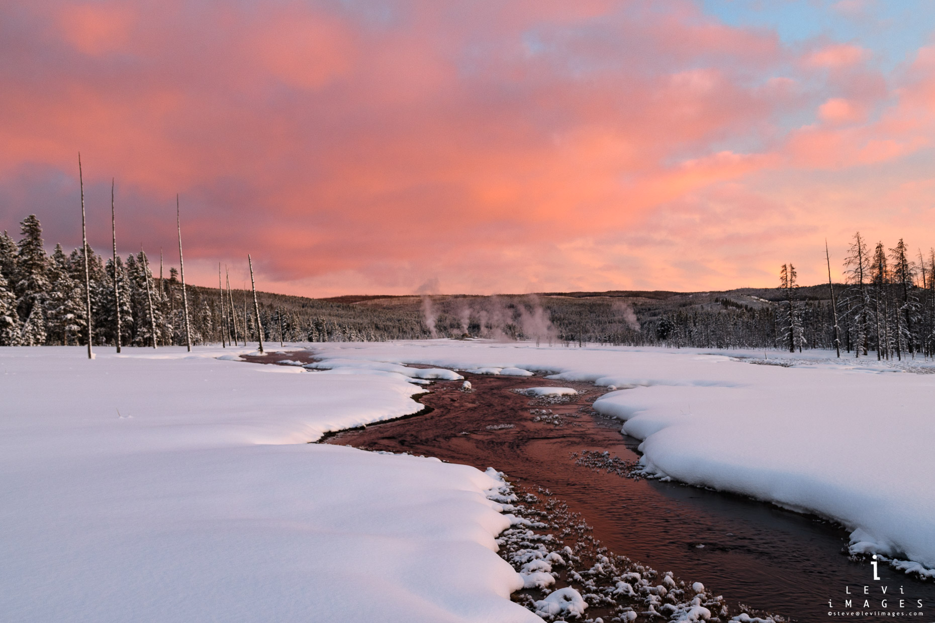 Sunset is reflected in stream with thermal features in the background. Yellowstone National Park, Wyoming